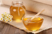 Honey in a glass bowl on a wooden boards background — Stock Photo