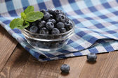 Fresh blueberries in a glass bowl on t — Stock Photo