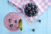 Yogurt with blueberries in a glass bowl and blueberries in a gla — Stock Photo