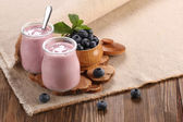 Yogurt with blueberries in a glass jar and blueberries in a wood — 图库照片