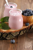Yogurt with blueberries in a glass jar and blueberries in a wood — Foto Stock