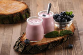 Yogurt with blueberries in a glass jar and blueberries in a glas — 图库照片