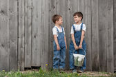Boys with brushes and paint at an old wall — Stock Photo