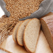 Bread cut on a board and a bag with wheat — Stock Photo #39295955