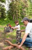 Vader en de zoon zagen van hout voor een brand — Stockfoto