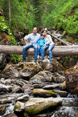 Family on a fallen tree across the river — Stock Photo