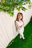 Teenage girl at the fence in the garden — Stock Photo