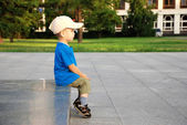 Boy sitting on a granite podium — Stockfoto