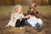 Boy and girl on haystack — Stock Photo