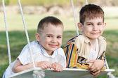 две счастливые мальчики на качелях — Стоковое фото