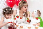 Mother and daughters sitting near the holiday table — Stock Photo