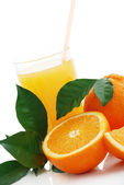 Orange juice and oranges — Stock Photo