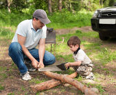 Father and the son cut wood for a fire — Stock Photo