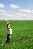 Girl enjoys a solar heat on a meadow — Stock fotografie