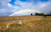 Beautiful full rainbow over road and mountain — Stock Photo