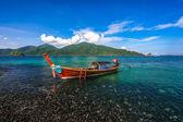 Long tail boat floating on beautiful pebble beach — Stock Photo