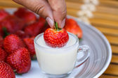 Strawberry in a cup of milk on bamboo table — Stock Photo