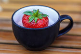 Strawberry in a cup of dessert on bamboo table — Stock Photo