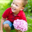 Stock Photo: Little boy with flowers