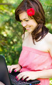 Young woman is playing on laptop — Stock Photo