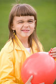 Little girl is inflating red balloon — Foto Stock