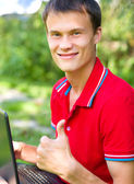 Young man is playing on laptop — Stock Photo