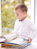 Little boy is reading book — Stockfoto