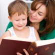 Stock Photo: Mother is reading book with her son