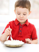 Cute little boy is eating cottage cheese — Stock Photo