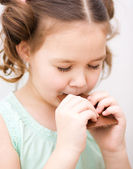 Cute girl is eating chocolate candy — Foto de Stock