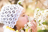 Little girl smelling flowers outdoors — Stock Photo
