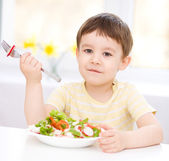 Cute little boy is eating vegetable salad — Stock Photo