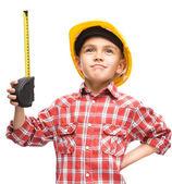 Pojken som en byggnadsarbetare med måttband — Stockfoto