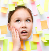 Cute girl with lots of reminder notes — Stock Photo