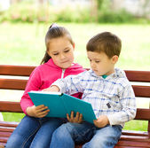 Little boy and girl is reading book — Stock Photo