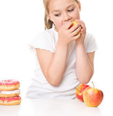 Cute girl choosing between apples and cake — Stock Photo