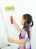 Girl as a construction worker with paint roller — Stock Photo