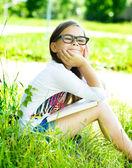 Klein meisje is het lezen van een boek buitenshuis — Stockfoto