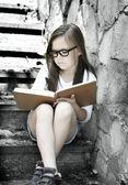 Dziewczynka jest czytanie książki na zewnątrz — Zdjęcie stockowe