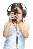 Little girl is enjoying music using headphones — Stock Photo