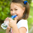 Cute girl drinks water from a plastic bottle — Stock Photo #50340151