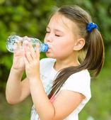 Jolie fille boit de l'eau provenant d'une bouteille en plastique — Photo