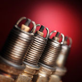 Old spark plugs on red background — Stock Photo