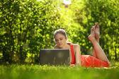 Giovane donna con il portatile sull'erba verde al parco — Foto Stock