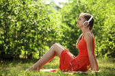 Young woman with headphones on green grass in the park — 图库照片
