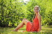Young woman with headphones on green grass in the park — Foto Stock