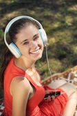 Young woman with headphones on green grass in the park — ストック写真