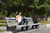 A young woman sitting on a bench, near the university, listenin — Stock Photo