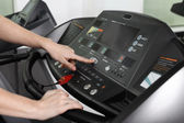Woman adjusts the treadmill at the beginning of training, do fit — Stock Photo