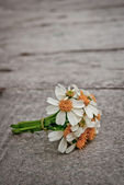 A small bouquet of white daisies on a wooden floor. — Stock Photo